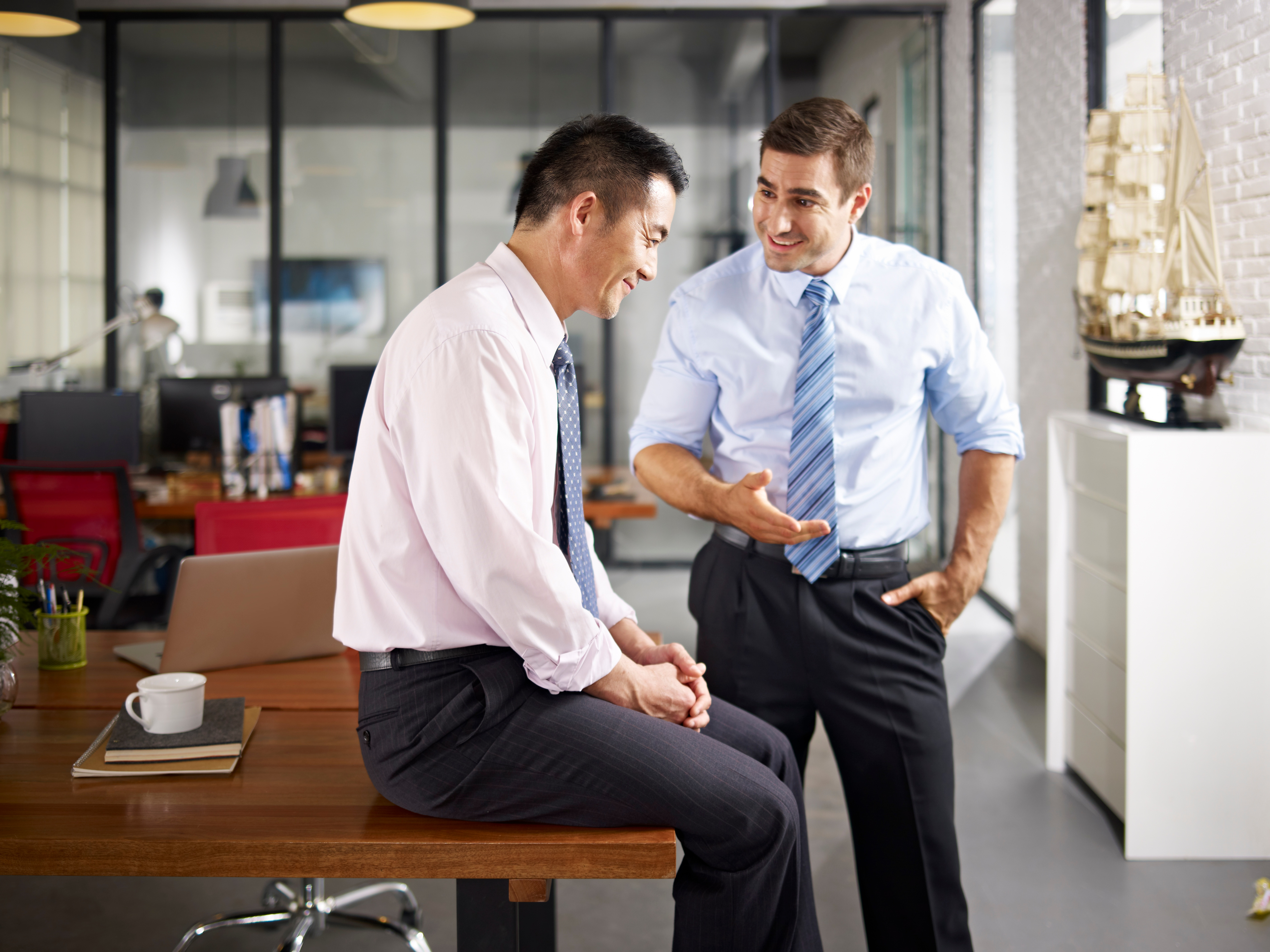 asian-and-caucasian-colleagues-talking-in-office-499721966_5620x4215